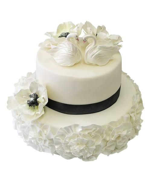 Белый двухъярусный свадебный торт с темной лентой , цветами и лебедями